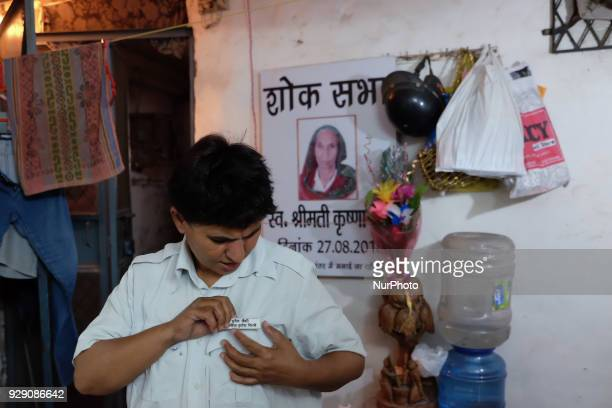 Sunita Choudhary North India's first autorickshaw driver puts on her badge as she prepares to leave for work from her house in South Delhi on 7th...