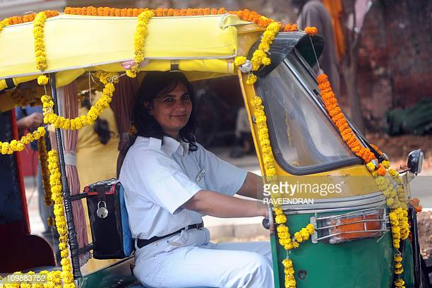 Sunita Choudhury the city's first woman autorickshaw driver smiles from her decorated autorickshaw in New Delhi on International Women's Day March 8...