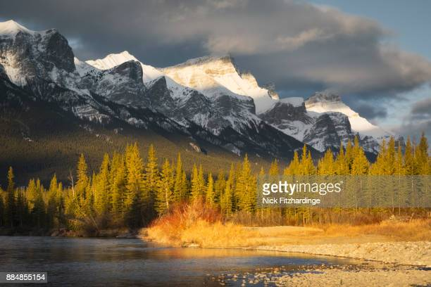 Sunlight along the edge of the Bow River and the Rundle Range, Canmore, Alberta, Canada