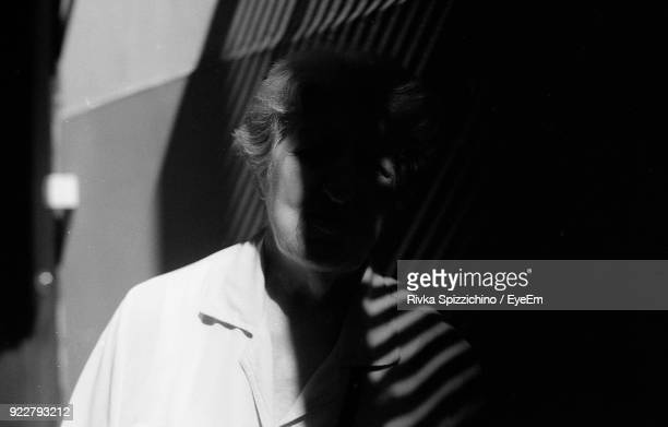 Sunlight And Shadow Falling On Senior Woman By Wall