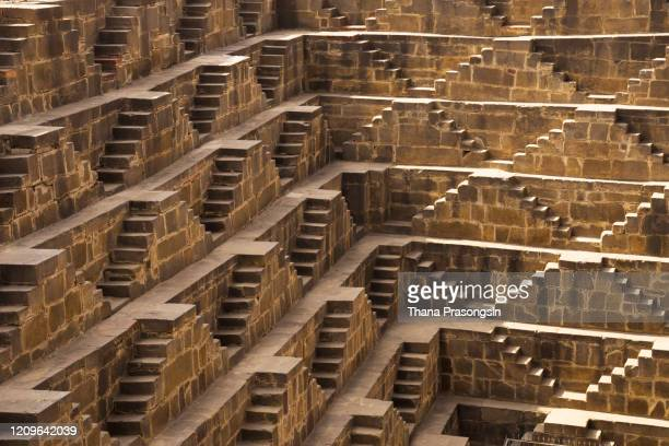 sunlight and shadows create attractive patterns at the chand baori stepwell, abhaneri, rajasthan, india - chand baori stock pictures, royalty-free photos & images