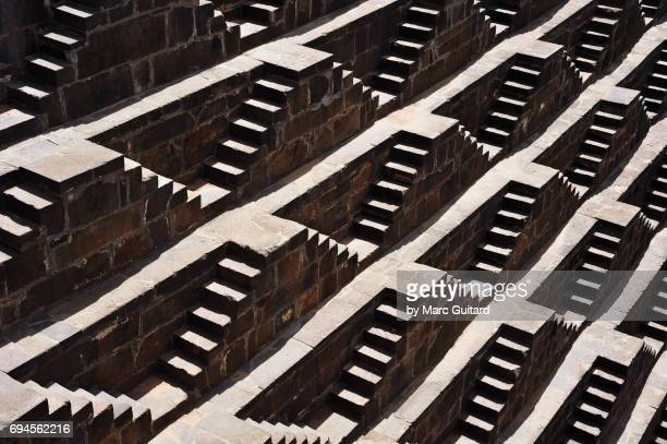 sunlight and shadows create attractive patterns at the chand baori stepwell, abhaneri, rajasthan, india - abhaneri stock photos and pictures