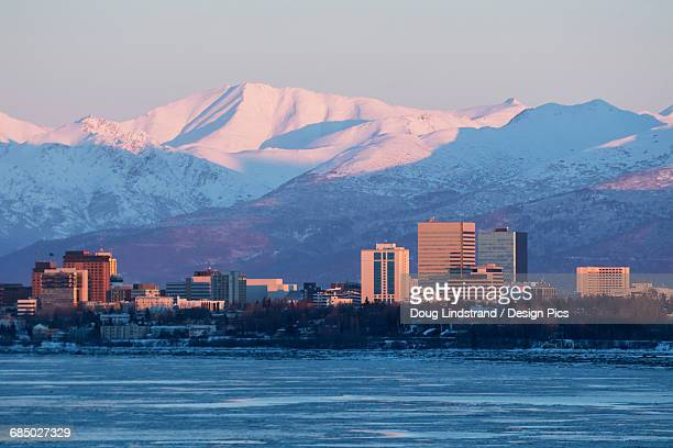 Sunlight at sunrise illuminating buildings and snow covered mountains in the background