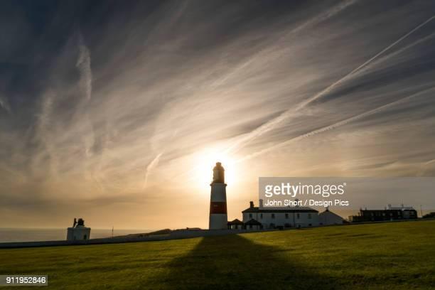 Sunlight Behind A Lighthouse Casts A Shadow On A Grass Field Along The Coast