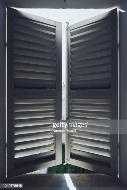 sunlight behind white wood shutters - fensterladen stock-fotos und bilder