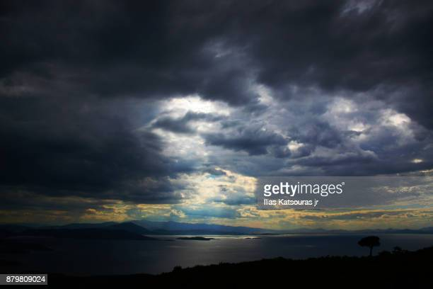 Sunlight breaks through storm clouds over Pagasitic bay in Greece