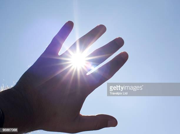 Sunlight bursting through fingers