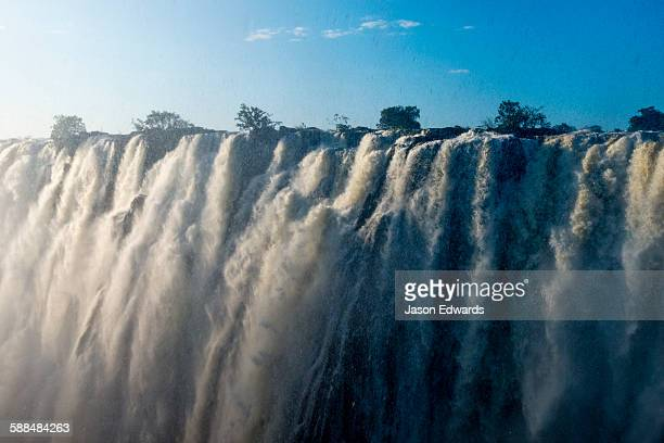Sunlight catches the cascading pillars of the Zambezi River as they pour over Victoria Falls.