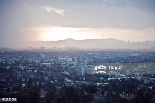 sunlight caught under impending storm clouds, oakland, california - oakland califórnia - fotografias e filmes do acervo