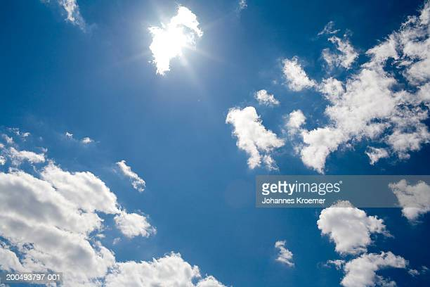 Sunlight emerging from behind cloud, low angle view (lens flare)