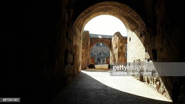 sunlight falling on archway of old building - inside the roman colosseum stock photos and pictures