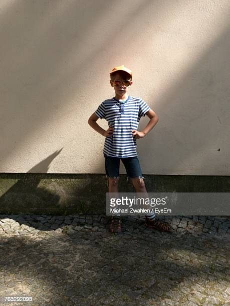 sunlight falling on boy standing by wall - arms akimbo stock pictures, royalty-free photos & images