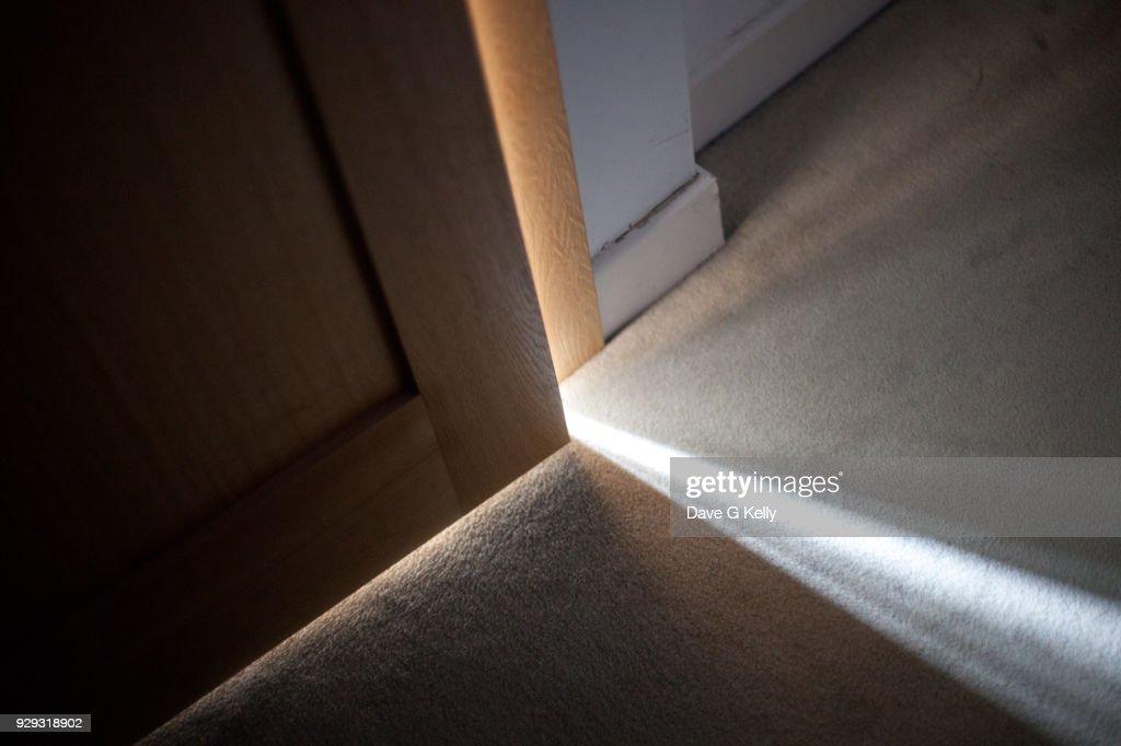 Sunlight falling on floor through A Door Ajar : Stock Photo