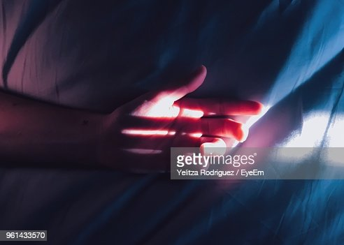 Sunlight Falling On Hand On Bed