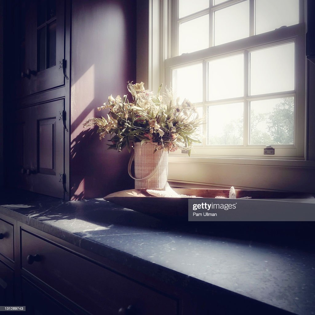 Sunlight falling on kitchen counter and bouquet : Stock Photo