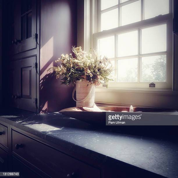 Sunlight falling on kitchen counter and bouquet
