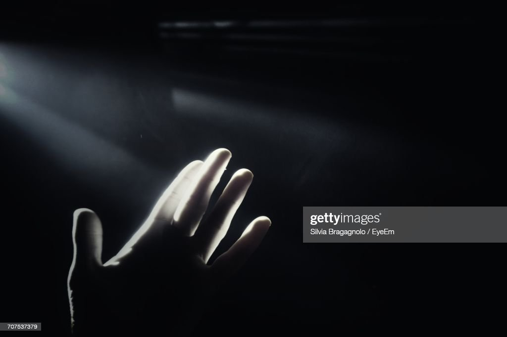Sunlight Falling On Person Hand In Darkroom Stock Photo