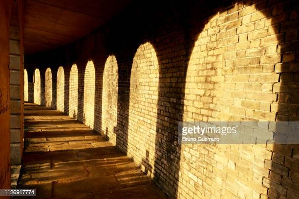 sunlight falling on stone wall at cemetery - arch architectural feature stock pictures, royalty-free photos & images