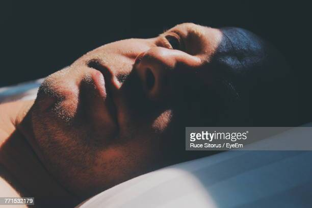 sunlight falling on thoughtful mid adult man lying on bed - lying down photos et images de collection