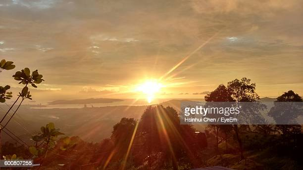 sunlight falling on trees against sky during sunrise - kota kinabalu stock pictures, royalty-free photos & images