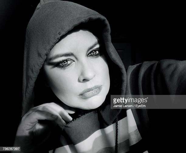 Sunlight Falling On Young Woman Wearing Hooded Shirt In Darkroom