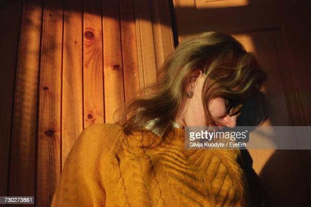 Sunlight Falling On Young Woman Wearing Sweater By Wooden Wall