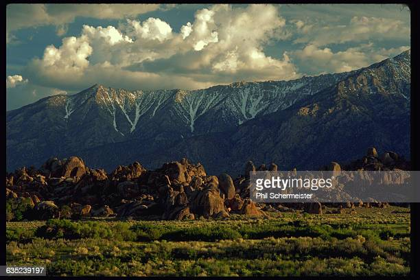 Sunlight falls over mountains in the Sierra Nevada Range and the rocky outcrops of the Alabama Hills west of Lone Pine California
