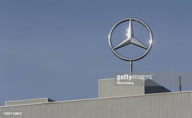 Sunlight glints off a MercedesBenz AG trident logo on the roof of the premium automaker's factory operated by Daimler AG in Rastatt Germany on Monday...