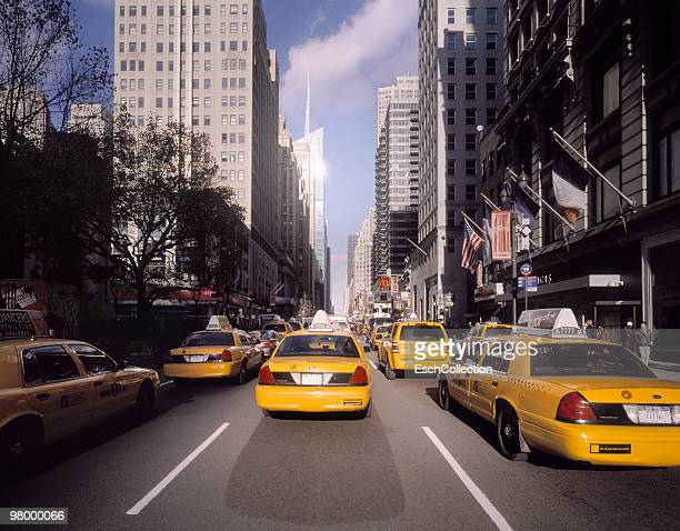 sunlight hitting busy taxi traffic in new york. - sixth avenue stock pictures, royalty-free photos & images