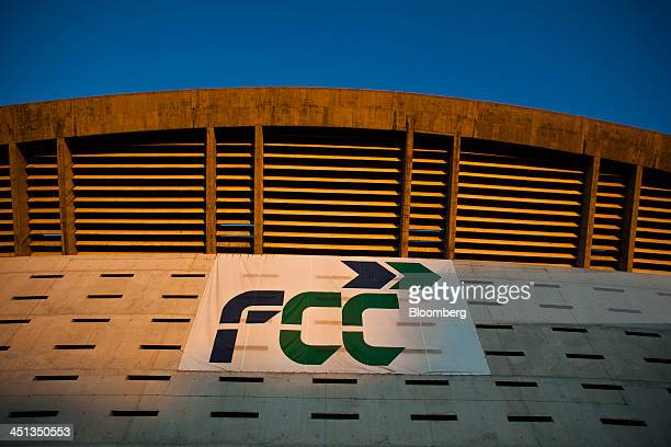 Sunlight illuminates an FCC logo hanging outside the partially built stadium at the La Peineta sports complex operated by Spanish builder Fomento de...