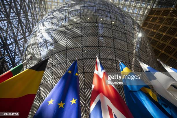 Sunlight illuminates European Union member state national flags ahead of a EU leaders summit in the Europa building in Brussels Belgium on Thursday...