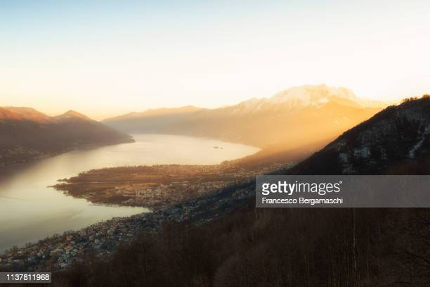 Sunlight illuminates the Lake Maggiore and villages of Ascona and Locarno. Canton of Ticino, Switzerland, Europe.
