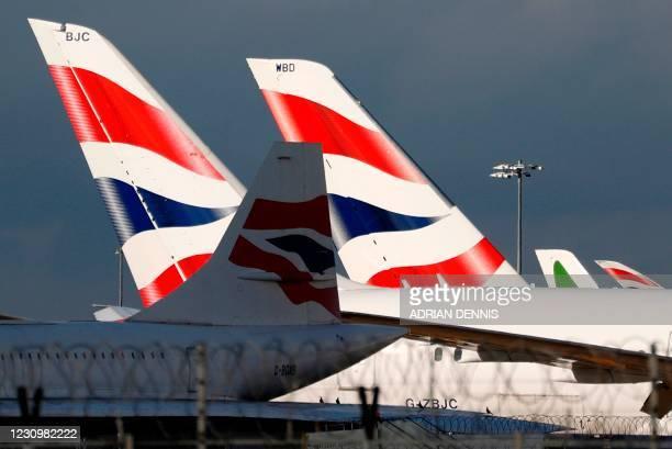 Sunlight illuminates the tailfins of British Airways aircraft at Terminal 5 of London Heathrow Airport in west London on February 5, 2021. - Britain...