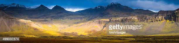 Sunlight illuminating dramatic mountain landscape snowy peaks Arctic pasture Iceland