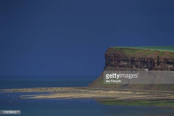 Sunlight lights up Huntcliff as dark storm clouds pass beyond it on June 27 2020 in Saltburn By The Sea England Thunderstorms have passed over some...