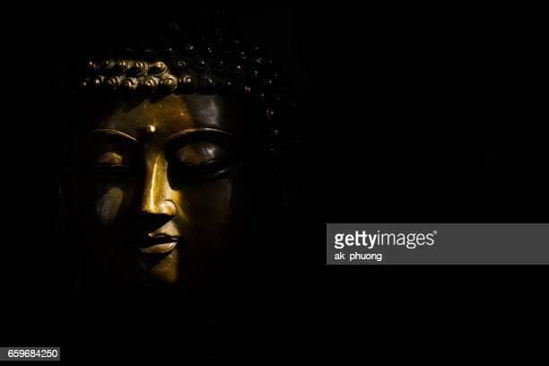 sunlight on buddha face against with black background - mondo beat foto e immagini stock