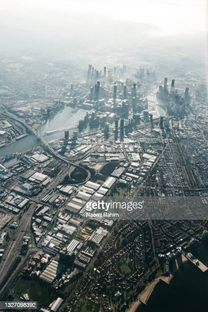 sunlight over melbourne cbd skyline and urban sprawl aerial view - docklands stadium melbourne stock pictures, royalty-free photos & images