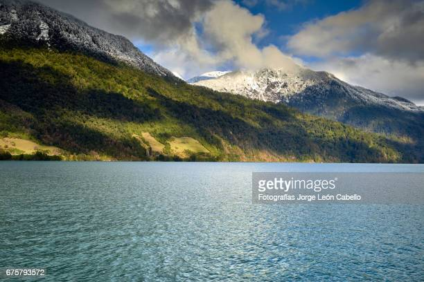 sunlight over the hills with clouds and snow during the winter andean lake crossing - azul turquesa stockfoto's en -beelden