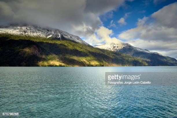 sunlight over the hills with clouds and snow during the winter andean lake crossing - azul turquesa stock pictures, royalty-free photos & images