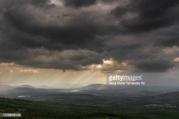 sunlight pierces through the dark clouds over beautiful landscape mountain. - calm before the storm stock pictures, royalty-free photos & images
