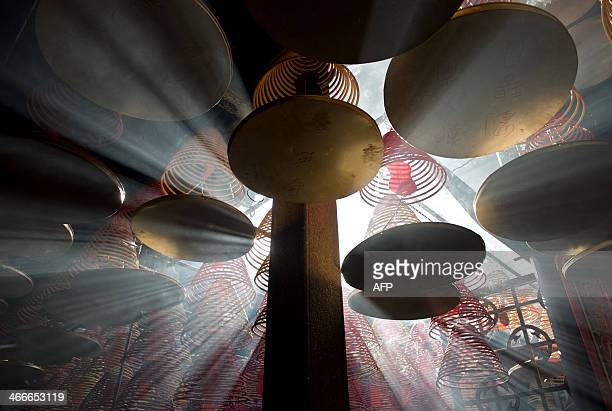 Sunlight shines through hanging incense coils at the Tin Hau Temple in the Yau Ma Tei area of Hong Kong on the fourth day of the Lunar New Year...