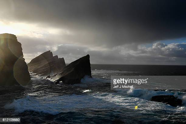 Sunlight shines through the cliffs on the Island of Foula on September 30 2016 in Foula Scotland Foula is the remotest inhabited island in Great...