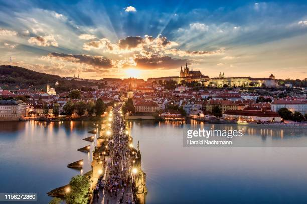 sunlight streaming on charles bridge, castle district, royal palace and st. vitus cathedral, prague, bohemia, czech republic - vltava river stock photos and pictures