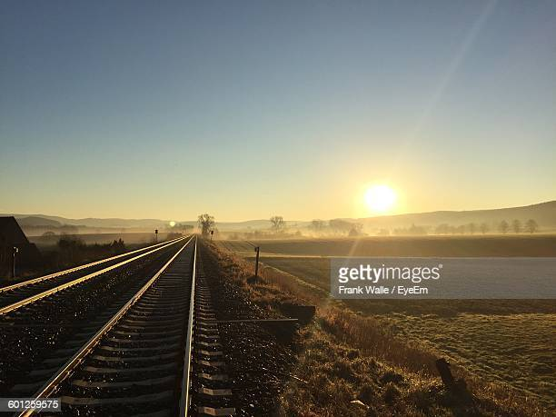 sunlight streaming on field by railroad tracks against clear sky - bahngleis stock-fotos und bilder