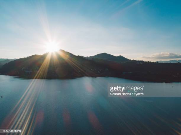 sunlight streaming through mountain against sky - bortes stock pictures, royalty-free photos & images