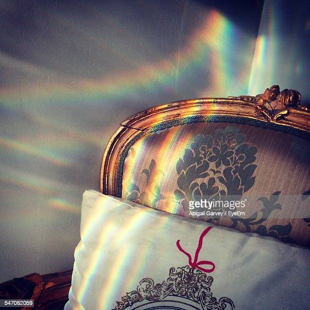 Sunlight Streaming Through Prism To Form Rainbow On Chair