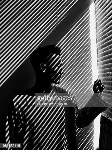Sunlight Streaming Through Window Blinds On Man
