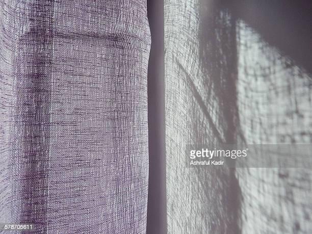 sunlight through a curtain creating lovely shadows - doorzichtige stof stockfoto's en -beelden