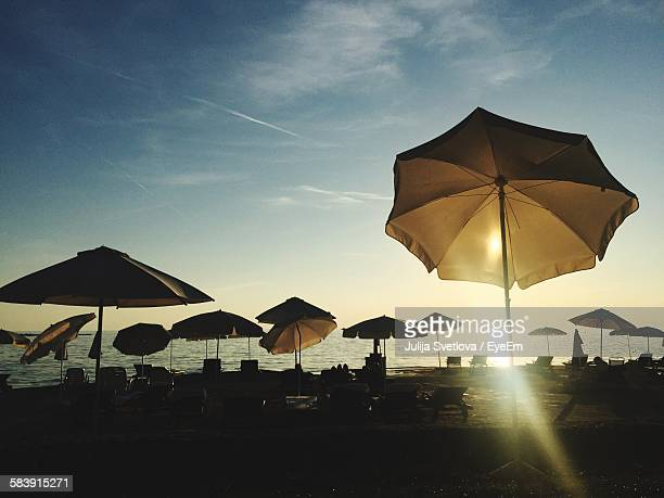 Sunlight Through Parasols On Beach Against Sky