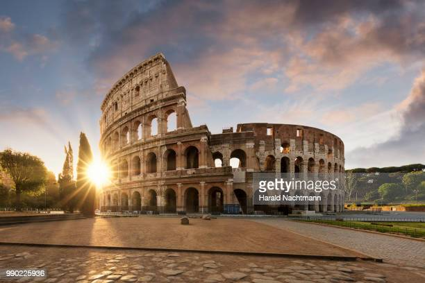 sunlight through the colosseum in rome - rom italien stock-fotos und bilder